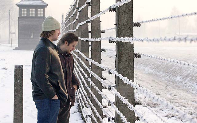World Stars Rhett Warrener, left, and Ray Whitney peer through the fence as they visit the Auschwitz-Birkenau World War II concentration camp.