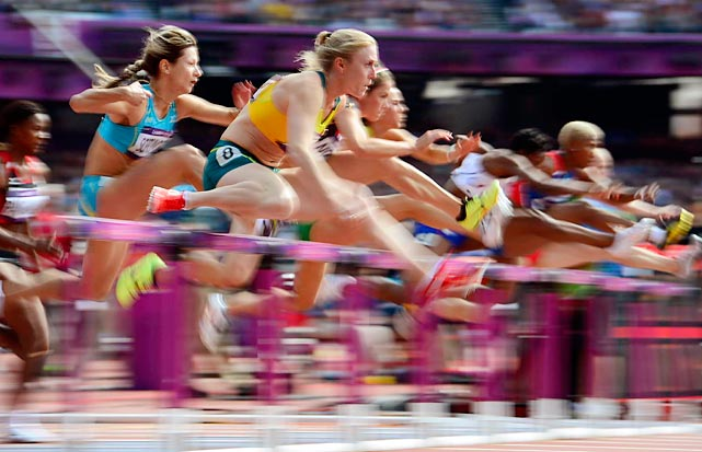 Olympians compete in the women's 100 meter hurdles preliminary race.
