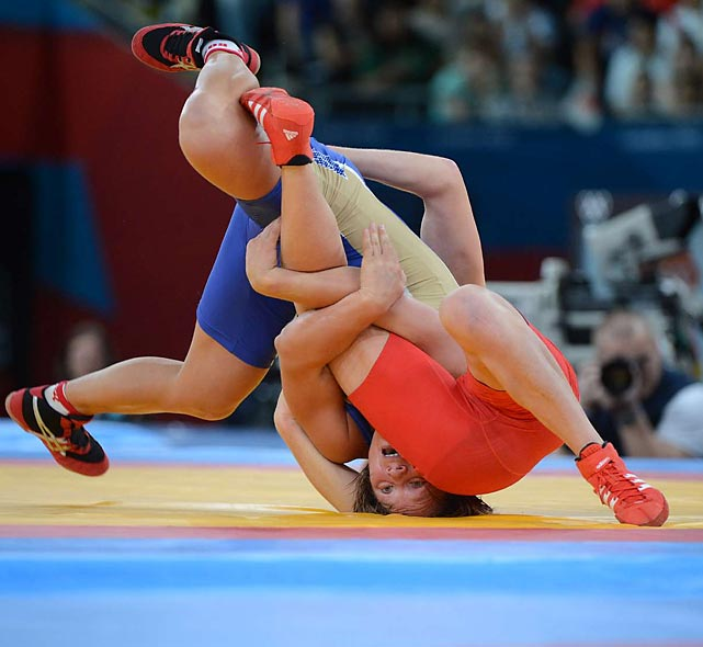 Russia's Lubov Volosova (in blue) tied up Poland's Monika Ewa Michalik  en route to winning their bronze medal match in the 63 kg class.