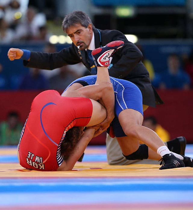 An official looks on while Olympians compete in the women's freestyle wrestling match.