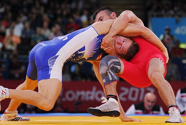 Ahmet Peker of Turkey (red) and David Tremblay of Canada wrestle during the 55kg freestyle division.