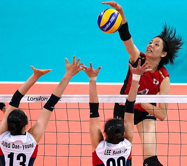 Saori Sakoda of Japan spikes against Dae-Young Jung (13) and Sook-Ja Lee of  Korea during Japan's 25-22, 26-24, 25-21 win for the bronze medal.