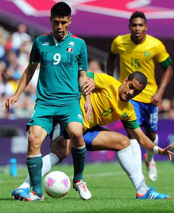 Oribe Peralta, challenged here by Romulo of Brazil, scored both of Mexico's goals, the first one coming 29 seconds into the match.