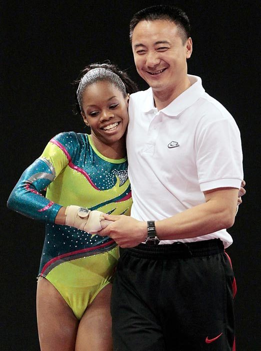 Douglas (left), who finished second overall, celebrates with her coach, Liang Chow, after successfully completing her vault during the U.S. gymnastics championships on June 10, 2012.