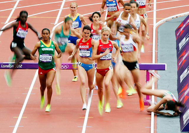 A runner during the 3000m steeplechase takes a tumble into the inside lane.