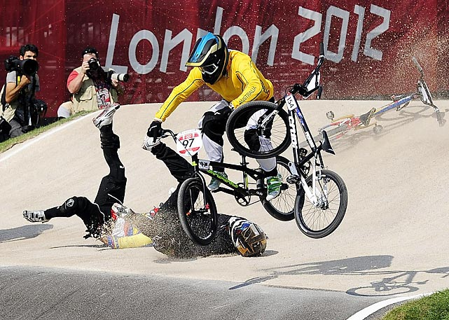 New Zealand's Kurt Pickard (black) and Ecuador's Emilio Andres Falla Buchley (yellow hat) collide and crash as Australian Olympian Khalen Young jumps over them in the BMX quarterfinals.