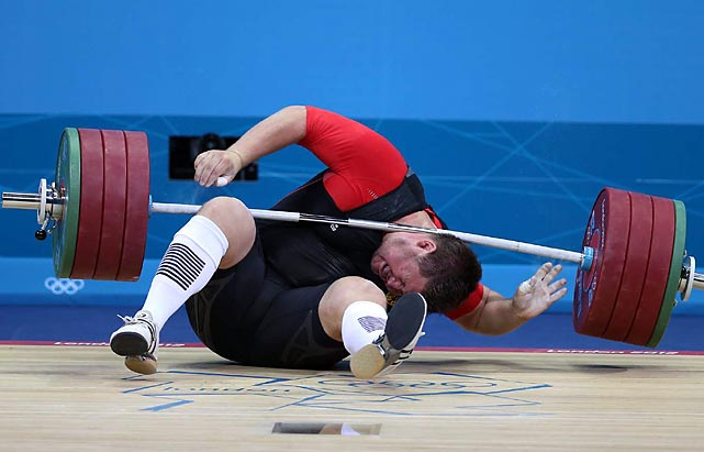 Germany's Matthias Steiner fails to lift the weight on his second attempts and falls, dropping the bar on his head.