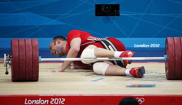 Ruslan Nurudinov of Uzbekistan falls after failing to hoist the weight during the men's 105kg competition.