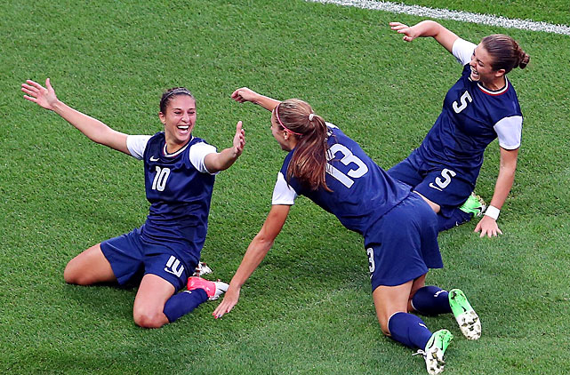Alex Morgan (13) and Kelley O'Hara rush in to congratulate Carli Lloyd. It was a pass by Morgan that led to the first goal.