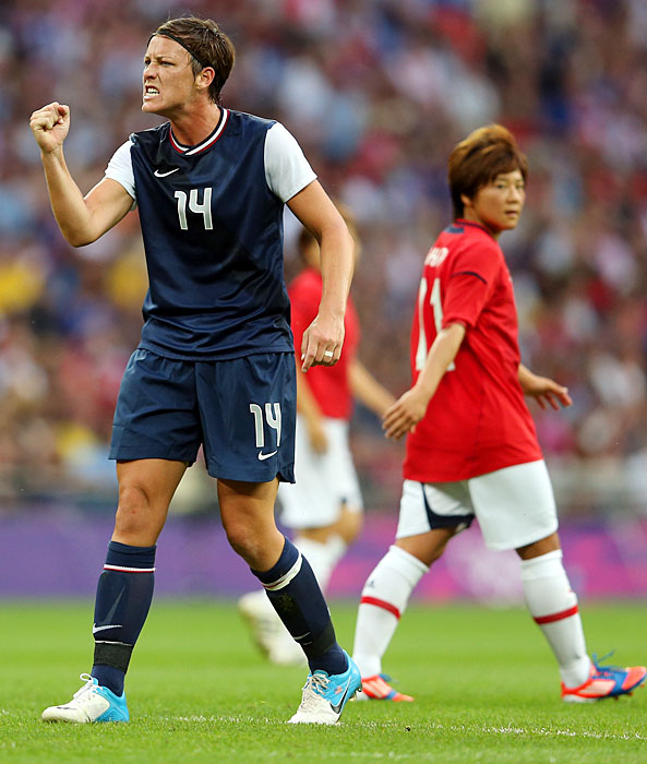 Abby Wambach reacts in the first half alongside Shinobu Ohno of Japan.