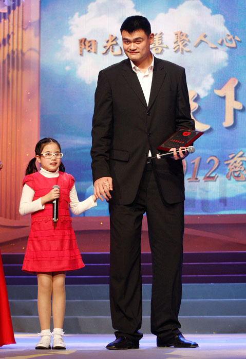 Yao stands next to a young student from Shanghai School for the Blind at a charity TV gala in Shanghai.