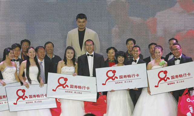 Happily married Yao Ming poses with eight couples of newlyweds during a collective wedding in Beijing.