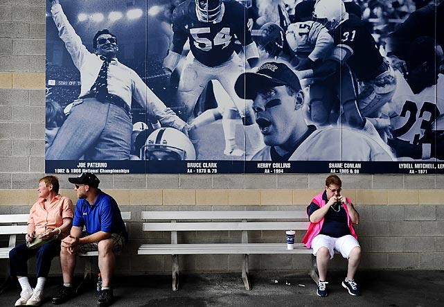 Fans sit in front of a sign inside Beaver Stadium featuring an image of former coach Joe Paterno celebrating.