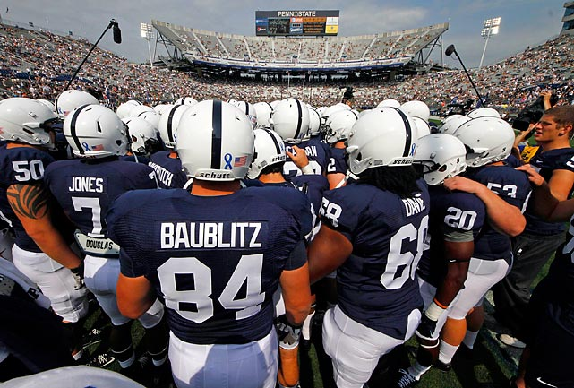 The Nittany Lions gather during warmups. The blue ribbon on their helmets is to support child abuse victims.