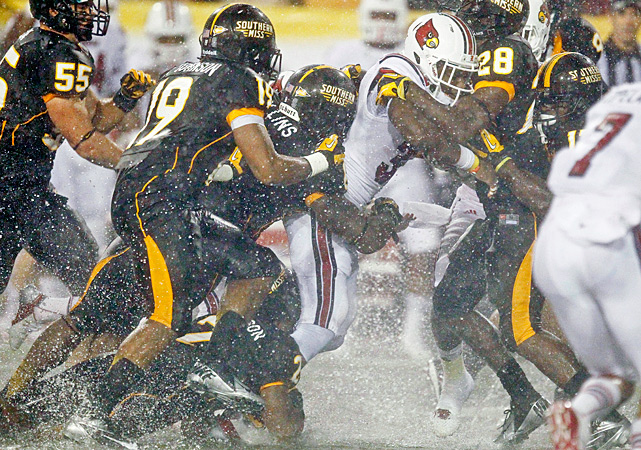 Senorise Perry (center) sloshed through the standing water and driving rain, bouncing off several Southern Miss defenders on his way to the end zone. With one last stumble, the 198-pound back lurched past the goal line and scored what proved to be the game-winning touchdown in Louisville's win at waterlogged Roberts Stadium. It wasn't pretty. Then again, nothing about this game will be remembered for artistry. Perry rushed for 118 yards and two touchdowns and Jeremy Wright added 84 rushing yards as the Cardinals (5-0) continued their best start since 2006.