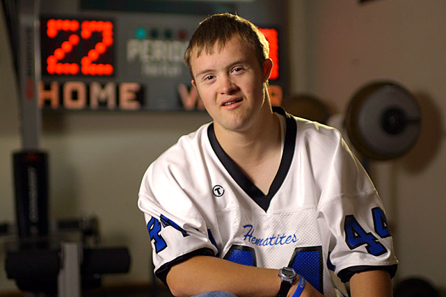 "For the fifth installment of the ""Underdogs"" series, SI.com travels to Ishpeming High in Michigan, where a school and its kicker are giving hope to a community. Eric Dompierre, a 19-year-old student with Down syndrome, was previously ruled ineligible for high school athletics. The Michigan High School Athletic Association (MHSAA) had regulations in place that barred any person who turned 19 before Sept. 1 from competing, and Dompierre, whose birthday falls over the summer and whose disabilities caused him to be held back twice early in his school career, landed on the wrong side of that deadline. He would be forced to watch from the stands instead of joining his teammates and friends on the sidelines.  An underdog his whole life, Dompierre was dealt another setback. But he and his father, Dean, didn't give up. They took to their case to state lawmakers with hopes of creating age-limit exemptions for students with disabilities.  In August, their persistence paid off. After more than two and a half years of petitioning the school and MHSAA, the Dompierres received the news: Eric's request for a waiver to keep playing football for Ishpeming had been granted.  Following last weekend's victory against Westwood, Mich., Ishpeming is 4-0. Here's a behind the scenes look at the Hematites -- and Eric. (To see the video on Ishpeming, click on the related link at the bottom right of this page)"