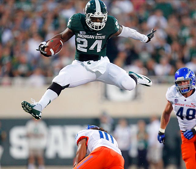 Le'Veon Bell of Michigan State leaps over Jeremy Ioane of Boise State during the Spartans' 17-13 win over the Broncos. It was the first time Boise State lost its opening game against a ranked opponent in four years.