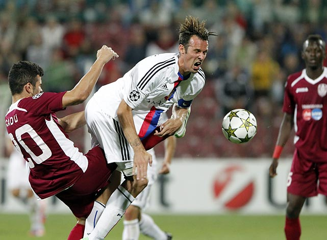 FC Basel's Marco Streller (center) and CFR Cluj's Cadu (left) collide, sending the ball and Streller's hair flying.