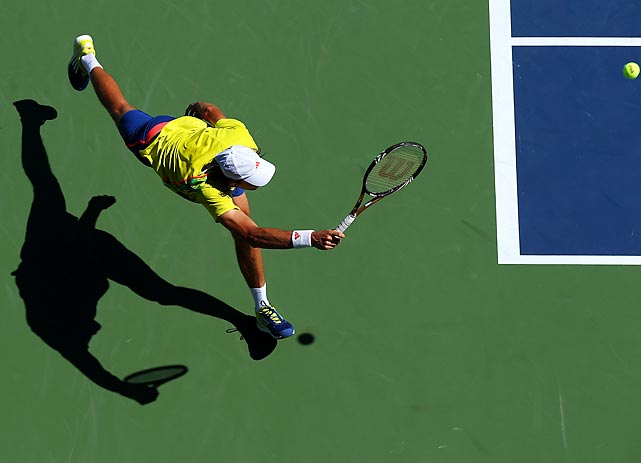 Guillaume Rufin of France stretches to play a forehand against Janko Tipsarevic of Serbia during their match at the U.S. Open.
