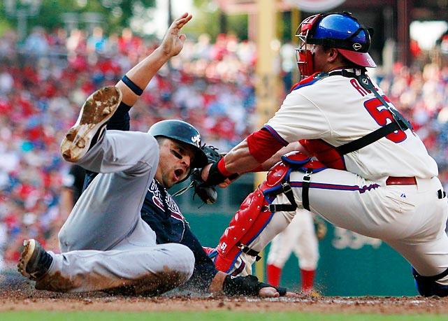 Atlanta Braves' Martin Prado scores past the tag of Philadelphia's Carlos Ruiz.