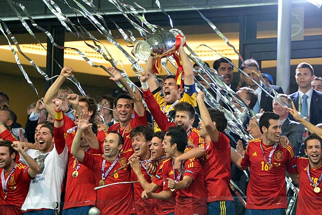 Spain became the first team to win three consecutive major titles (Euro 2008, World Cup 2010, Euro 2012) after thrashing Italy 4-0 in the European final. Playing a thrilling brand of end-to-end soccer, the Spaniards scored two wondrous goals to start and two more goals late to overwhelm an aggressive but overmatched Italian side.