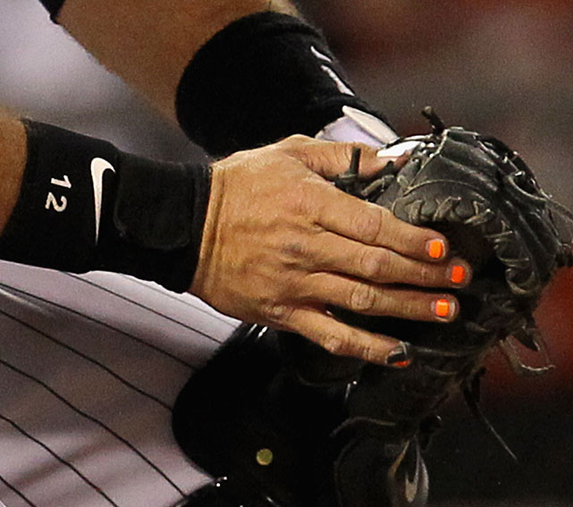 No, White Sox catcher A.J. Pierzynski isn't using his nails to show off his Halloween spirit. They are painted orange to help the pitcher see his signals better, a common practice among MLB catchers.