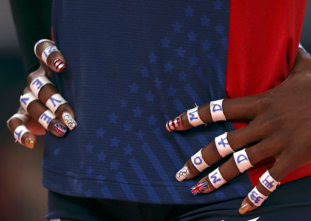 U.S. volleyball star Destinee Hooker honors the UK, American and Olympics flags during the 2012 Games in London.