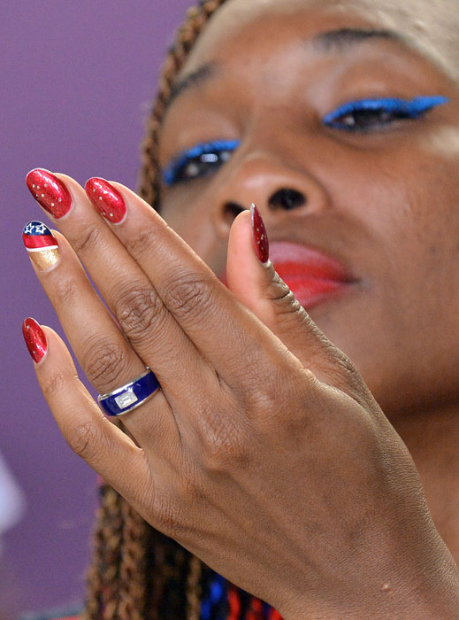 Venus Williams, a certified nail technician, looks at her fingernails during a press conference at the Olympic Stadium before the start of the 2012 Games.