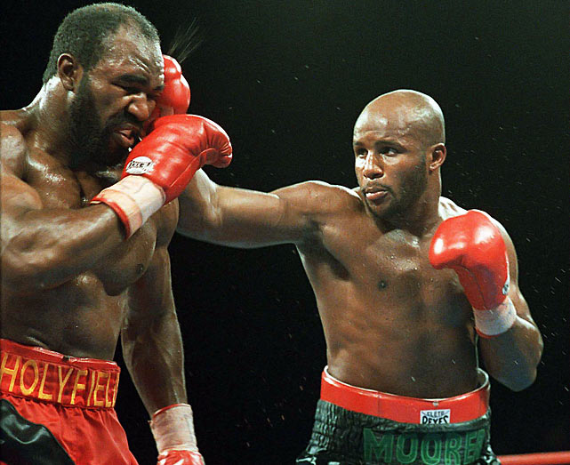 Moorer was born in Brooklyn and grew up in Pennsylvania before coming under the tutelage of Emanuel Steward at the famed Kronk Gym in Detroit.  Moorer stopped Ramzi Hassan in five for the vacant WBO Light Heavyweight title in 1988.  Moving to Heavyweight, Moorer stopped Bert Cooper in 1992 to win the WBO Heavyweight belt.  A decision over Evander Holyfield in 1994 made him the first southpaw universally recognized as heavyweight world champion.  Moorer would later win a vacant IBF belt with a decision over Axel Schultz in 1996.