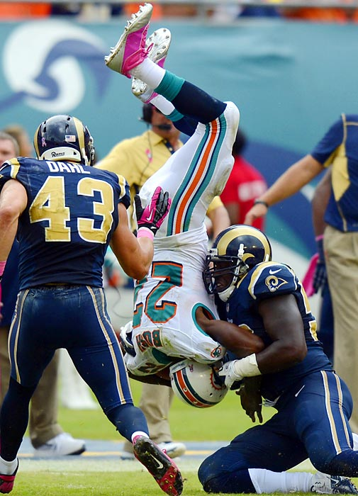 Dolphins running back Reggie Bush is upended during Miami's 17-14 win over the St. Louis Rams.