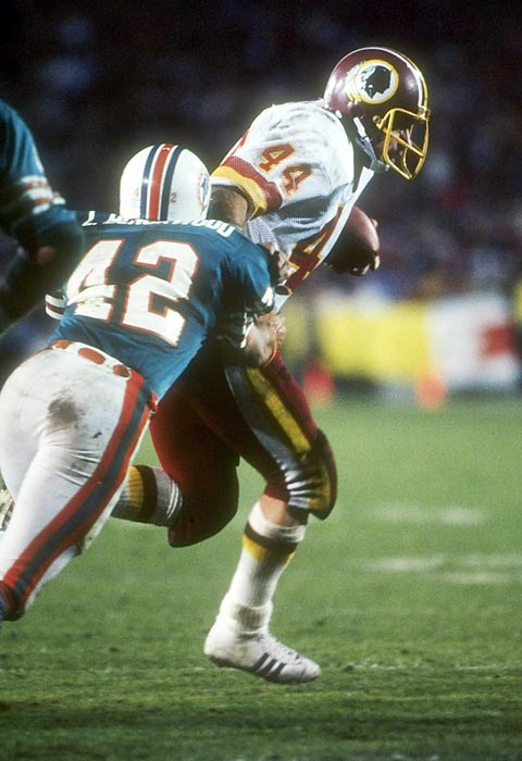 "John Riggins' Super Bowl record 166 yards rushing and fourth-quarter 43-yard touchdown burst on a fourth-and-one call give the Redskins their first Super Bowl crown and first NFL championship in 40 years, a 27-17 win over the Miami Dolphins. Washington's famed ""Hogs"" offensive line pulverized the Miami defense for 276 yards rushing."
