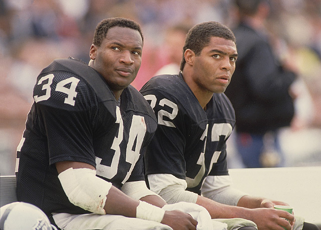 Jackson sits on the bench next to teammate Marcus Allen during Jackson's rookie season of 1987.