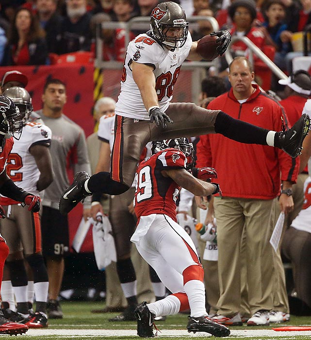 Tampa Bay tight end Luke Stocker hurdles over linebacker Stephen Nicholas during the first half of an NFL football game Sunday, Dec. 30, 2012, in Atlanta. The Bucs won, 22-17, but still finished the season with a losing record.