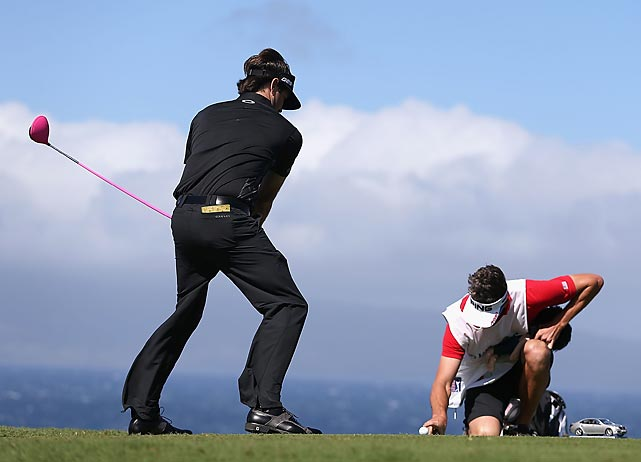 Bubba Watson pretends to tee off while his caddie, Ted Scott, holds a finger on the ball to keep it from blowing away on the 10th hole during a replay of the first round of the Hyundai Tournament of Champions. The players battled high winds that forced tournament officials to cancel play on the first two days.