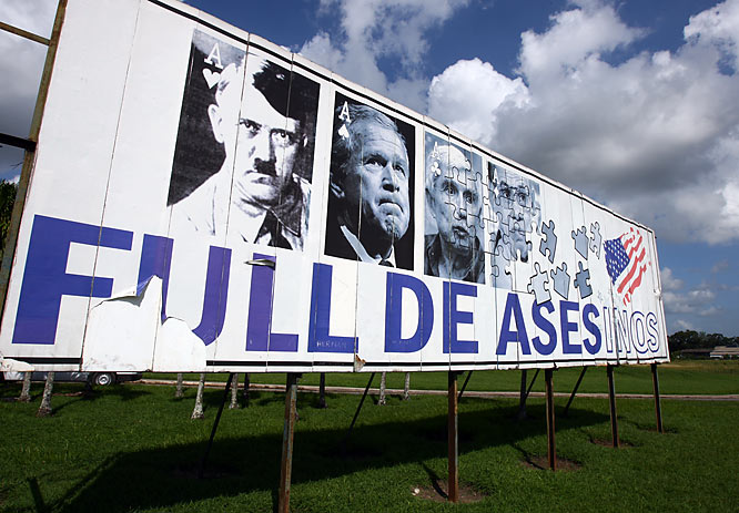 """One of the first things the U.S. soccer team saw on the road leaving the Havana airport on Thursday was a giant billboard featuring President George W. Bush next to Adolf Hitler, the late Cuban-exile leader Jorge Mas Canosa and Orlando Bosch. """"Full De Asesinos"""" has a double meaning: """"Ases"""" means *Aces* (note the playing card theme, an echo of the U.S.-produced playing cards showing ex-Iraqi leaders), while """"Asesinos"""" means *Murderers*."""