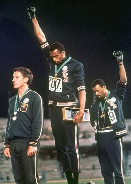During a medal ceremony at the Summer Olympics in Mexico City, Tommie Smith and John Carlos famously  give the black power salute.