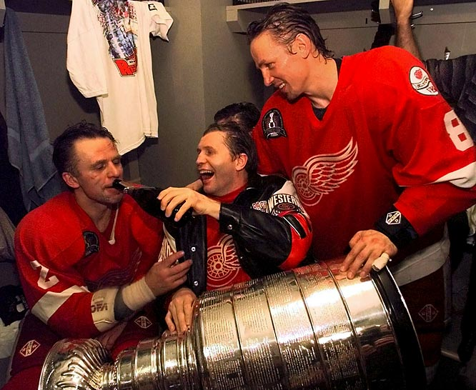 Vladimir Konstantinov holds the Stanley Cup in his lap and pours champagne for defenseman Viacheslav Fetisov, left, as center Igor Larionov looks on after the Red Wings beat the Capitals, 4-1, in Game 4 of the 1998 Stanley Cup Finals.