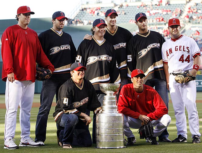 Members of the 2007 Stanley Cup champion Anaheim Ducks pose with Los Angeles Angels pitchers John Lackey (left), Scot Shields (kneeling) and catcher Mike Napoli before a game.