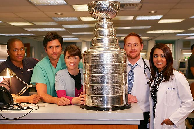"Cast members of ""ER"" pose with the Stanley Cup on the set of their hit show."