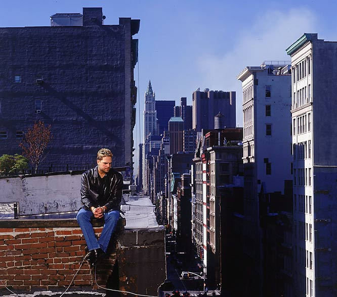 Mike Piazza sits on a rooftop near the World Trade Center disaster five days after the terrorist attacks of 9/11. The plume of smoke in the upper-right hand corner comes from the site and the Twin towers would have been able to have been seen above the middle buildings.