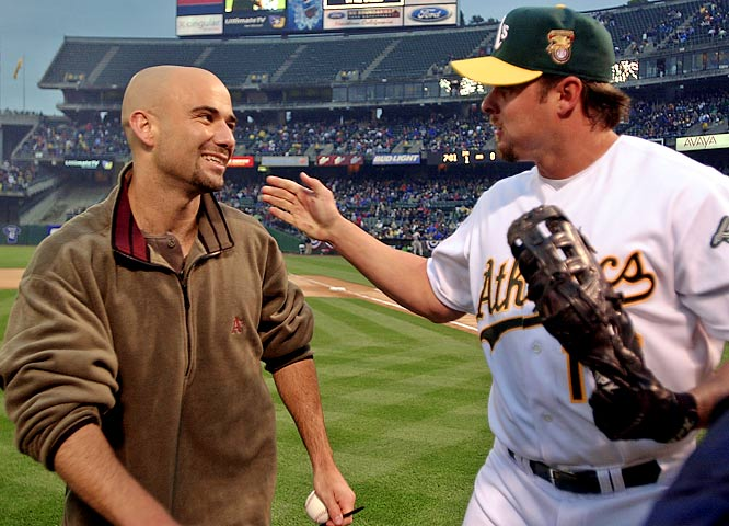 Andre Agassi gets a pat on the back from Jason Giambi after throwing out the first pitch in the A's home opener.