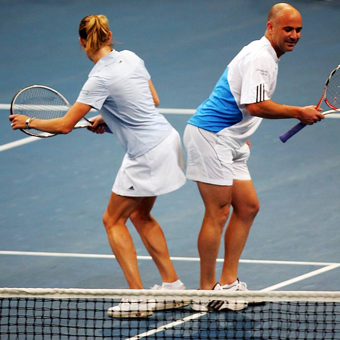 Steffi Graf and Andre Agassi exchange a unique high five during the Festival for Children benefit match in Mannheim, Germany.