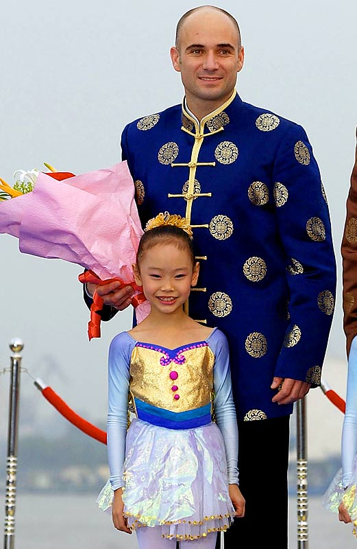 Andre Agassi poses with a young Chinese host during the Tennis Masters Cup in Shanghai.