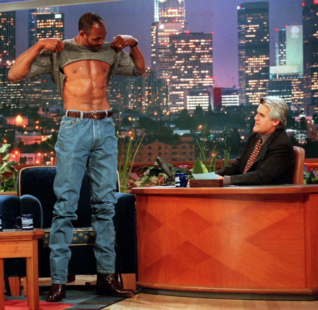 """As Jay Leno prepares to move back to his 11:30 p.m. time slot, we look back at some memorable appearances by athletes on """"The Tonight Show with Jay Leno"""" during its original run from 1992 to 2009. In this photo, Karl Malone shows off his stomach muscles after Leno poked fun at The Mailman's fitness video."""