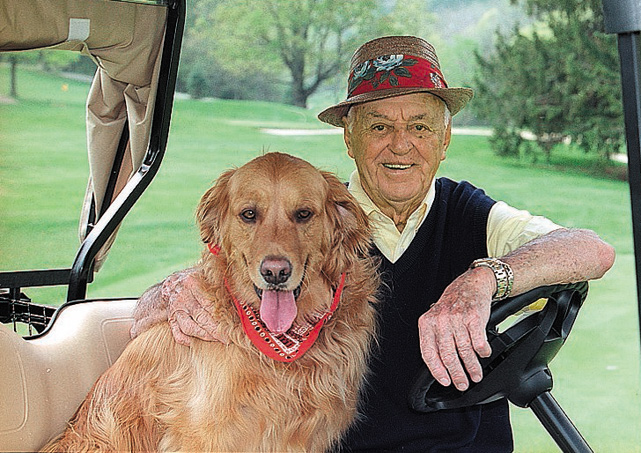 Sam Snead and Buddy pose while sitting in a golf cart.