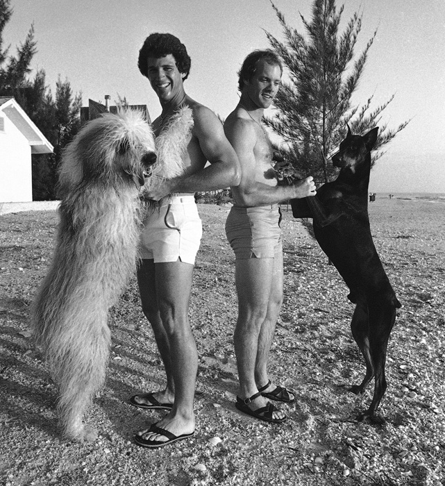 New York Mets teammates Doug Flynn (left) and Joel Youngblood play with their dogs during spring training in St. Petersburg Beach, Fla.
