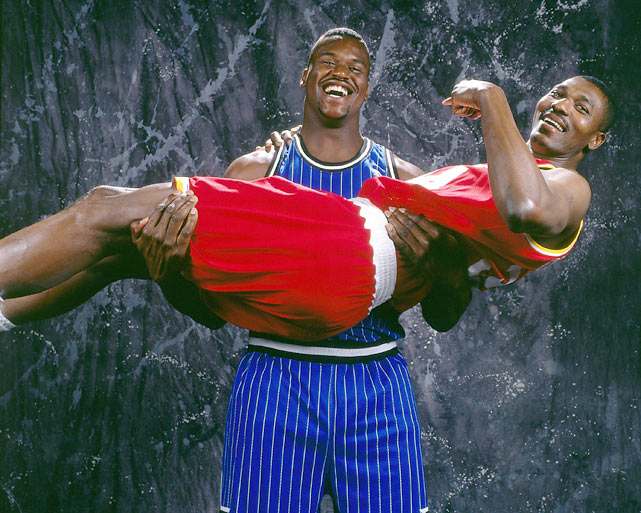 Hakeem Olajuwon relaxes in the arms of Shaquille O'Neal.