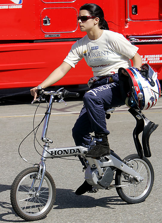 Patrick rides a bike down to the pits before a practice session at the Toyota Indy 400 in Fontana, Calif.