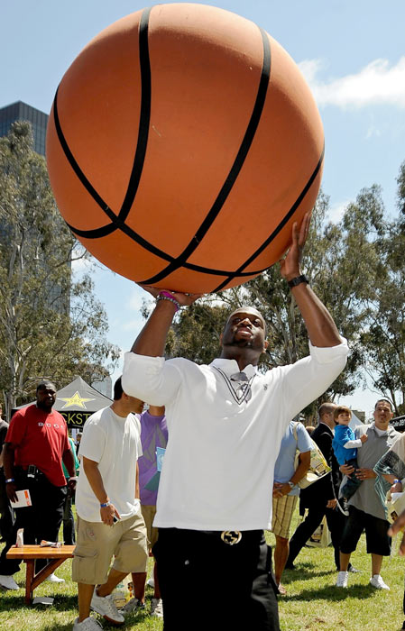 Wade shoots an oversized basketball during the Time for Heroes Celebrity Carnival in Los Angeles.