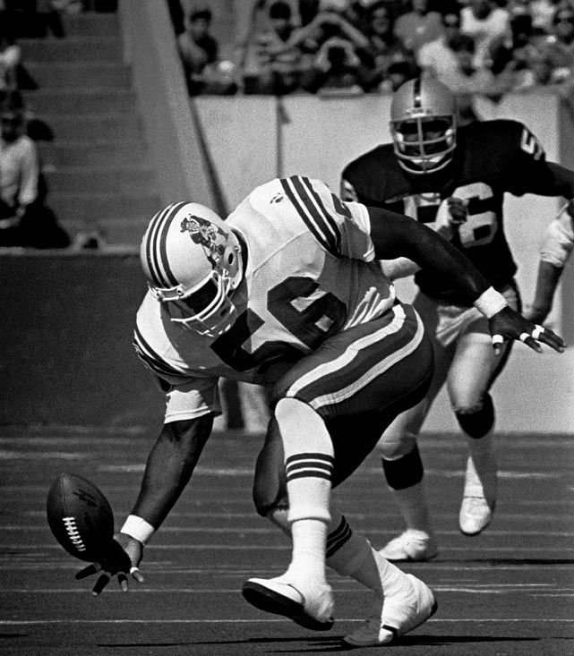 Hall of Fame linebacker Andre Tippett tries to get the handle on a Ray Guy fumble on a punt attempt during New England's 35-20 loss to the Raiders in Foxboro.  Tippett recovered the fumble and returned it 25 yards for a touchdown.